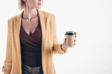 cropped view of trendy woman holding coffee to go on grey