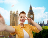 people concept - smiling red haired teenage girl in checkered shirt taking selfie and showing peace over big ben in london background