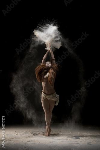 fototapeta na ścianę Female dancer throwing sand over head