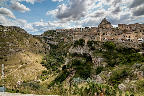 Summer day scenery street view of the amazing ancient town of the Sassi with white puffy clouds moving on the Italian blue sky. Matera, Basilicata, Italy - 262748612