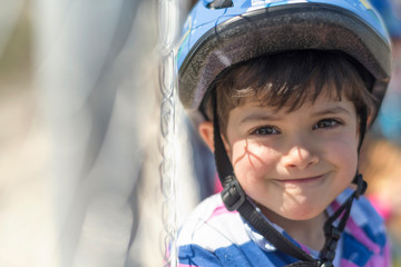 Biker kid near to fences smiling an dlooking at camera