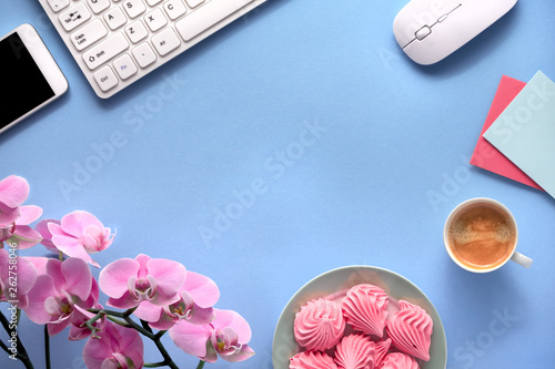 Feminine working space with pink orchids, keyboard, mobile phone, plate of marshmallow and cup of coffee