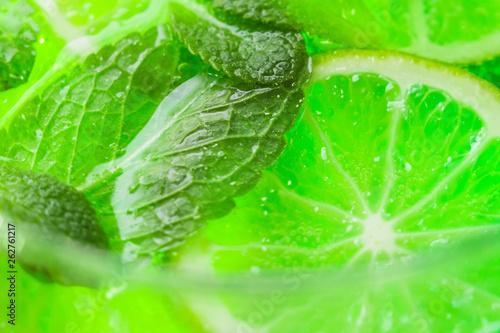 Leinwandbild Motiv mint and lime in cocktail close-up
