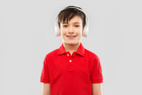 technology, audio and people concept - portrait of smiling little boy in red polo t-shirt and headphones listening to music over grey background