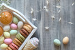 Easter flat lay with macarons, muffins and marzipan eggs jn a decorative tray on textured grey wood - 262768078