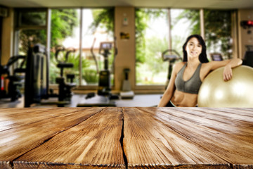 Desk of free space for your decoration and slim young woman in gym interior.