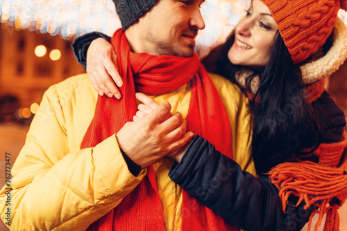 canvas print picture Winter evening, smiling love couple hugs on street