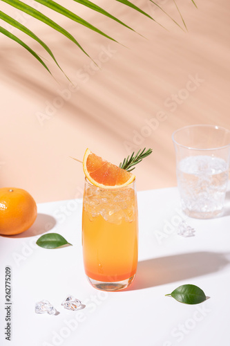 canvas print picture Cold and refreshing orange punch cocktail with orange slice on color background. summer drink.