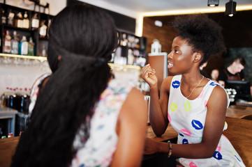 Two black african girlfriends at summer dresses drinking milkshake cocktails in bar.