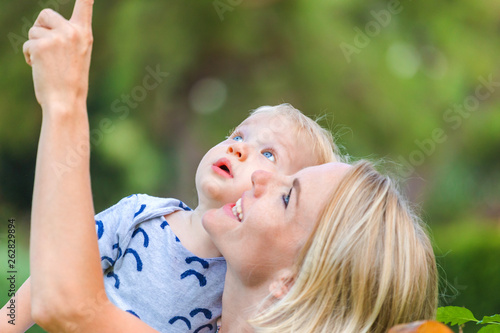 canvas print picture Mom shows something in the sky to her little baby boy