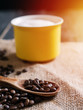Yellow cappuccino coffee mug and coffee beans in wooden spoon
