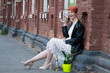 Young red-haired woman in a white dress sitting on the street and drinking white wine