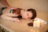 lateral view of a beautiful woman in spa salon having spa therapy with coffee done by a masseur