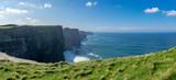Vue panoramique d'une succession de falaises d'Irlande avec de l'herbe verte en premier plan