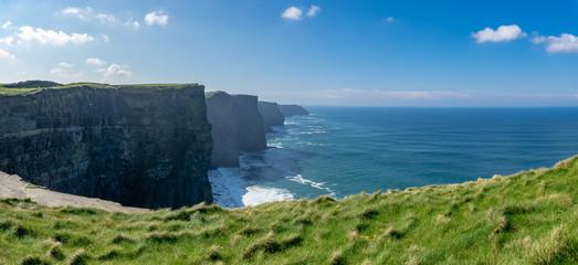 Vue panoramique d'une succession de falaises d'Irlande avec de l'herbe verte en premier plan © Olivier Tabary