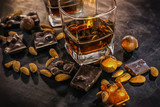Glasses of whiskey, chocolate with hazelnuts, candy and almonds on a dark wooden background.