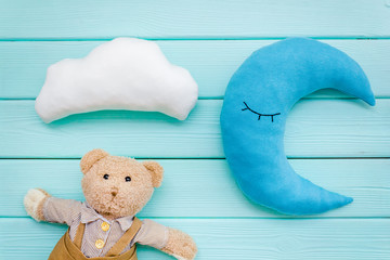 Baby care concept with moon pillow, clouds, teddy bear and toy for sleep of newborn on mint green background top view