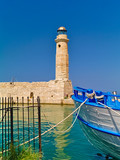 Rethymno port lighthouse and white blue boat. Bright summer day.