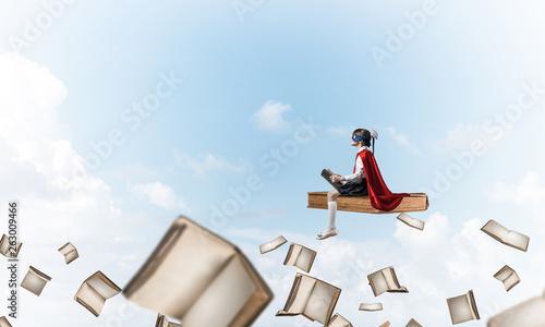 Leinwandbild Motiv Girl power concept with cute kid guardian against cloudscape background