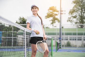 Tennis players playing a match on the court . Young woman playing tennis on court.
