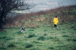 Pretty blonde woman and yellow raincoat walking on green meadow with Siberian Husky dog.