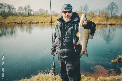 Leinwandbild Motiv Fisherman holds asp in hand.