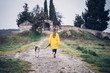 Pretty blonde woman and yellow raincoat walking on road with Siberian Husky dog.