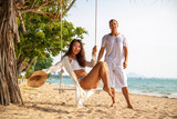 Multinational couple relaxing on the beach in Thailand. The woman sit on swings, man behind