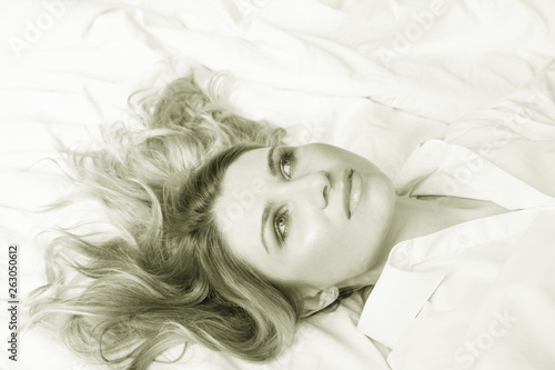 canvas print picture portrait of a beautiful woman with white hair in the bedroom on the bed sepia toned