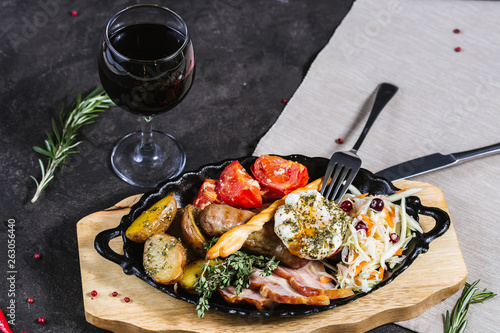 Hot assorted meats, bacon, meat sausages with roasted tomatoes, potatoes, poached egg and fresh cabbage on a platter, with a glass of red wine on a dark background - 263056440