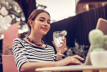 Delighted positive woman holding a delicious cocktail
