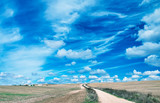 Beautiful windy countryside road against blue sky with clouds. Holiday and vacation concept - 263079277