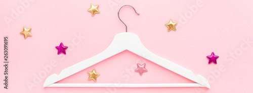 White hangers on pastel pink background