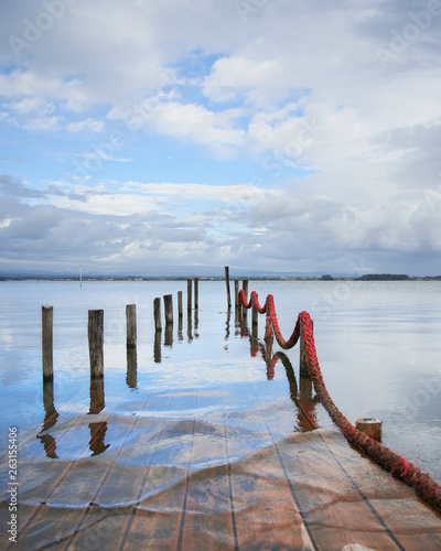 Wooden lake pier submerged by the water of Aveiro lagoon , under the cloudy sky and with a red rope on the side at Torreira, Portugal © Aldrin