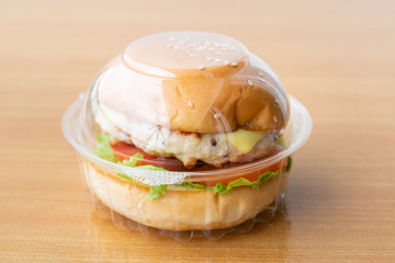 Chicken burger with cheese,lettuce and tomato in clear plastic box.