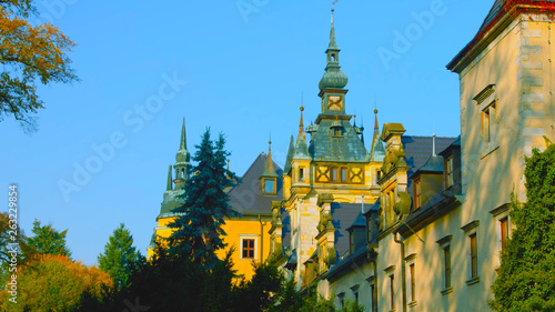Wawel castle in Krakow, Poland. Towers . Picturesque territory in autumn day with yellow and green trees. Blue sky with clouds.