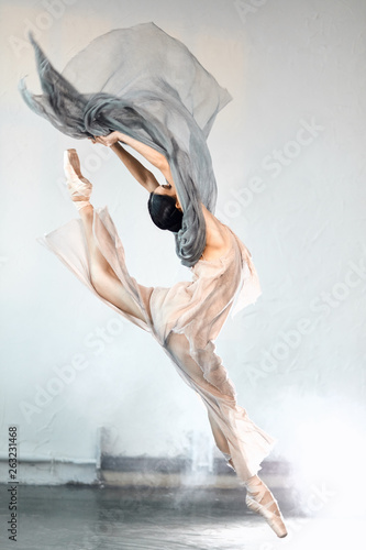 Adorable dar-haired female dancer performing on scene her part of concert jumping high in the air expressing emotions and beauty of classical ballet. Concert performance dance. © alfa27
