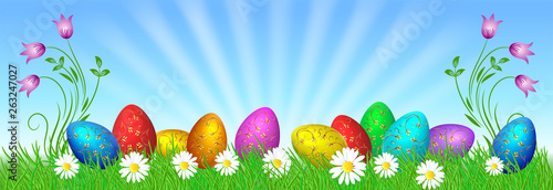 Easter eggs with golden ornament on green grass and rays in blue sky - 263247027