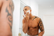 Reflection of man applying shaving foam in bathroom