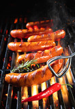 Delicious sausages sizzling over the coals on barbecue grill