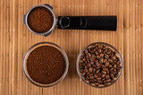Holder from coffee maker with coffee, bowl with fried coffee beans, bowl with ground coffee on mat. Top view