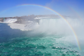 Rainbow over the Horseshoe Falls over frozen ice and snow on the Niagara River in Niagara Falls in March 2019 © eqroy