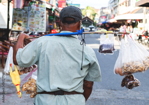 Pattaya, Thailand - March 24, 2019: Thai street vendor selling snacks on a street. Walking hawker guy with lots of food from the back.