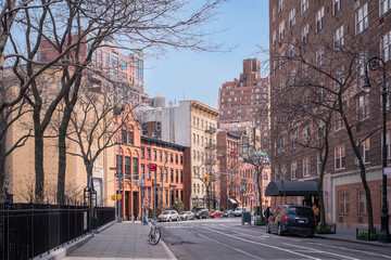 A corner of Greenwich Ave in New York's Greenwich Village with iconic brick buildings and cars parked along an empty street