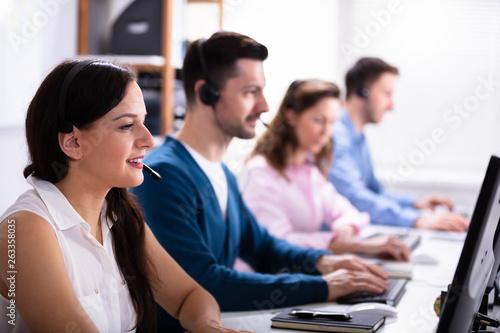 Smiling Customer Service Executives Using Earphones © Andrey Popov