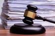 Leinwandbild Motiv Judge Gavel In Front Of Stacked Files On Table