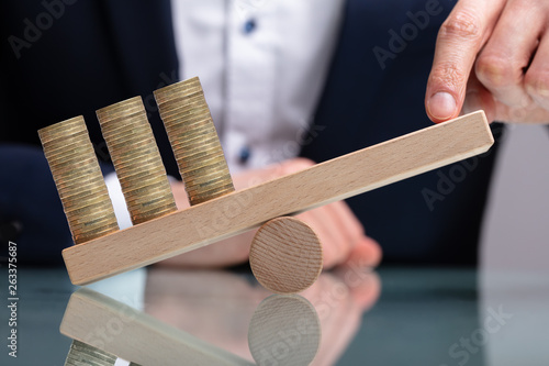 Businessman Balancing Stacked Coins With Finger © Andrey Popov