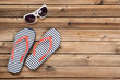 Pair of flip flops with sunglasses on brown wooden table
