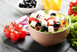 Vegetable salad in bowl with tomatoes on wooden table