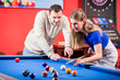 Woman receiving advice on shooting pool ball while playing billiards